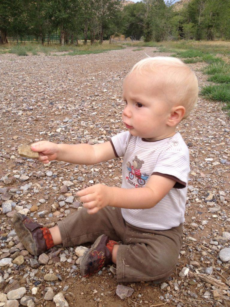 toddler playing on rock path