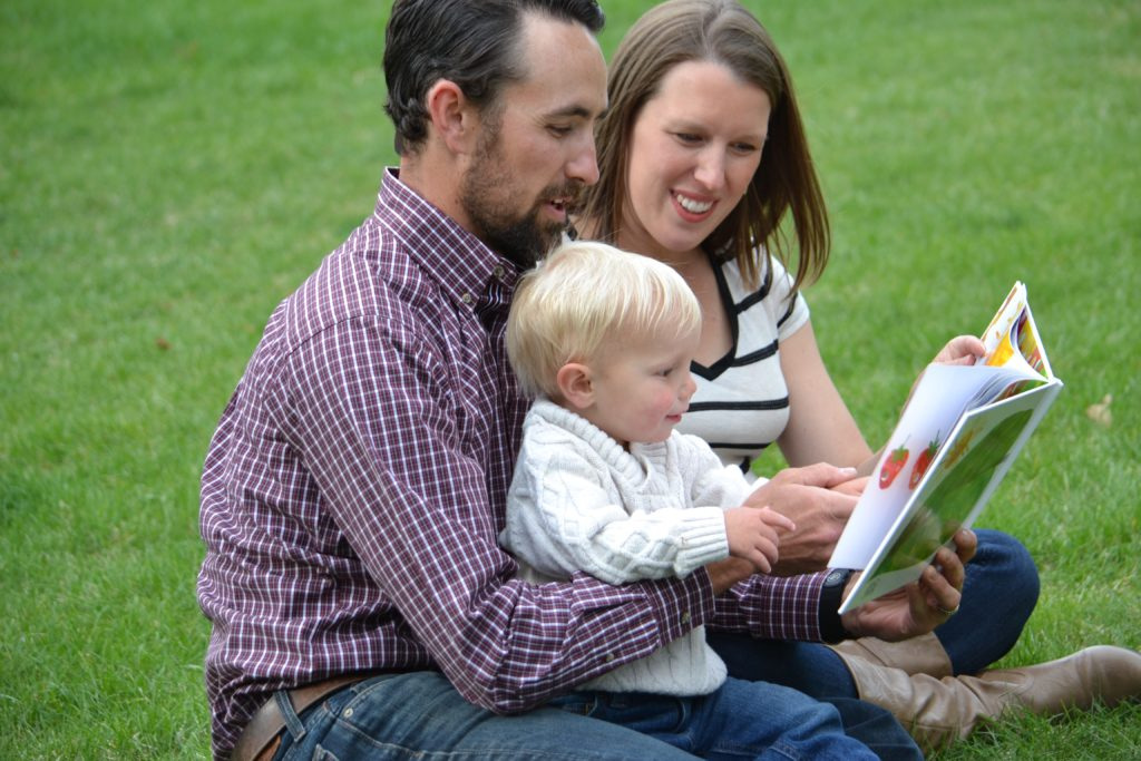 Mom, Dad and son reading a book in the grass