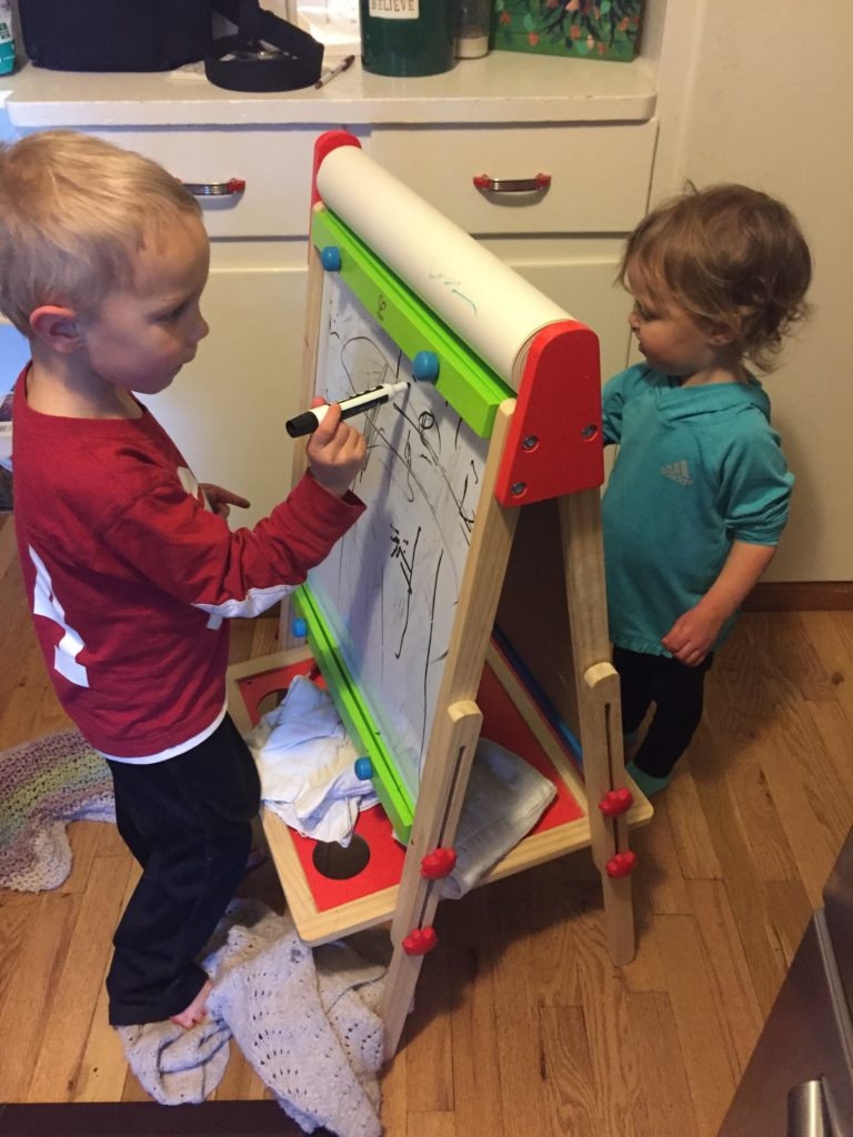 Two kids painting together on an easel